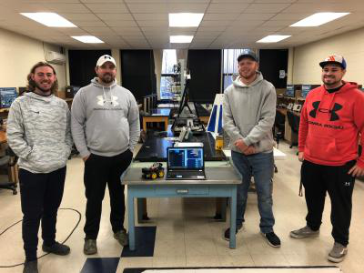 007比分网直播 students (left-to-right) Mason Van Dyke, Caige Clark, David Cavins, and Hunter Hill pose with a microprocessor smart robot-vehicle they created during the fall semester's ELET-Microprocessors course at BSC.